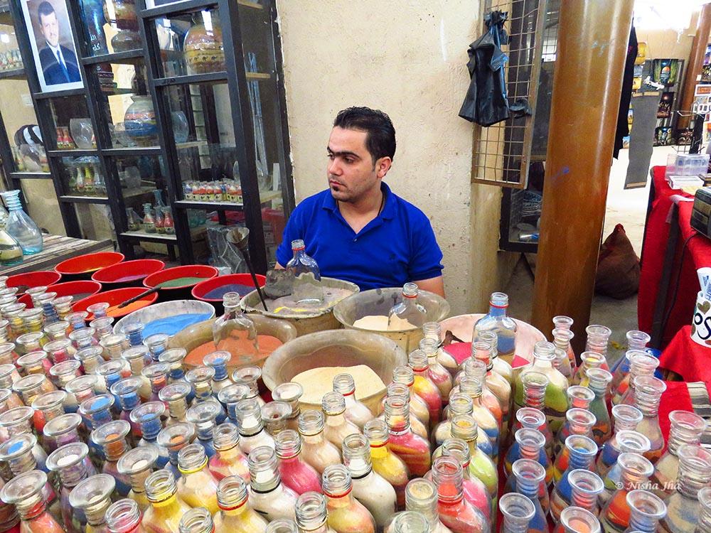 An artist cum shopkeeper waiting for customers